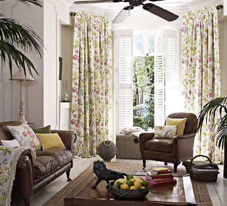 Prestigious Textiles -  Paradise Fabric Collection - Pink, green and cream floral curtains and cushions with a dark brown sofa and armchair, a wood table and yellow cushions