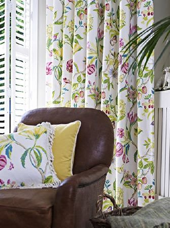Prestigious Textiles -  Paradise Fabric Collection - A brown leather armchair with a yellow cushion and pink, green and white floral patterned curtains and a fringed cushion