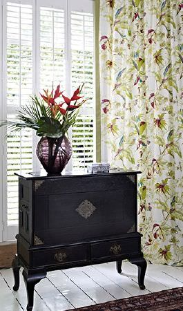 Prestigious Textiles -  Paradise Fabric Collection - A grand black chest with gold details, a large purple glass vase and white, green and purple floral patterned curtains