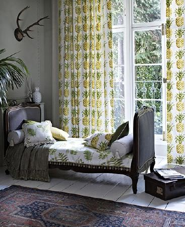 Prestigious Textiles -  Paradise Fabric Collection - Pineapple print fabric made into curtains, cushions and a seat for a dark wood sofa bed, with a dark patterned rug