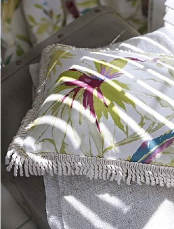 Prestigious Textiles -  Paradise Fabric Collection - Fringing around a white, green and pink floral cushion, on a light grey throw folded up overa dark grey chest
