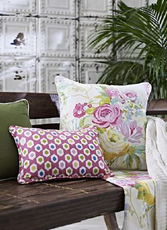 Prestigious Textiles -  Paradise Fabric Collection - Pink, green, blue and white floral, patterned and plain cushions with floral and white throws on a dark wood bench