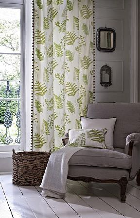 Prestigious Textiles -  Paradise Fabric Collection - White and green fern print curtains with pompoms with a matching cushion, a white cushion and a throw on a grey armchair