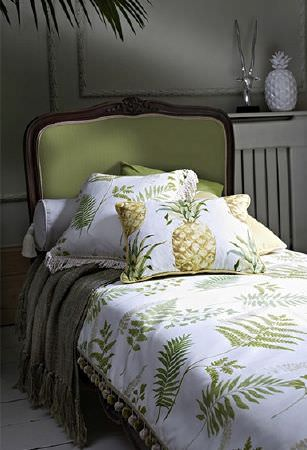 Prestigious Textiles -  Paradise Fabric Collection - Light green, wood framed sofa bed with a fern print throw with pompom edging, pineapple print cushions and a grey blanket