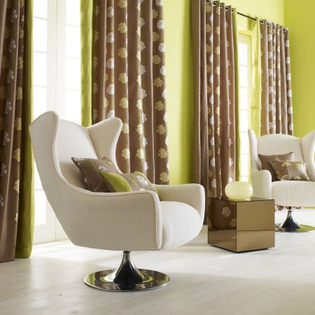Prestigious Textiles -  Passion Fabric Collection - Modern white upholstered easy chair with brown and green cushions, and brown and green curtains with a gold floral pattern