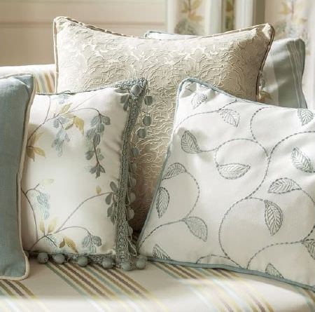 Prestigious Textiles -  Pemberley Fabric Collection - Pale blue and cream cushions with different floral designs, one with bobble fringing, on a coordinating striped sofa