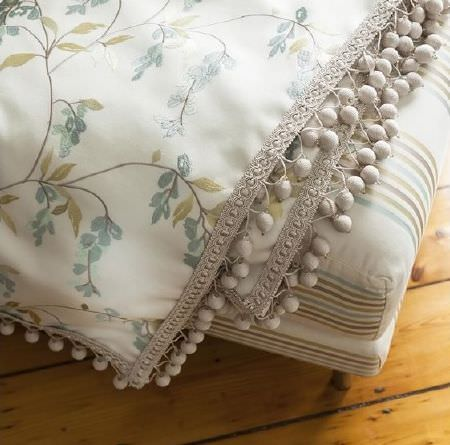 Prestigious Textiles -  Pemberley Fabric Collection - Seat cushions with cream, blue, green-grey and beige stripes, and fabric featuring the same coloured florals and cream pompoms on the edge