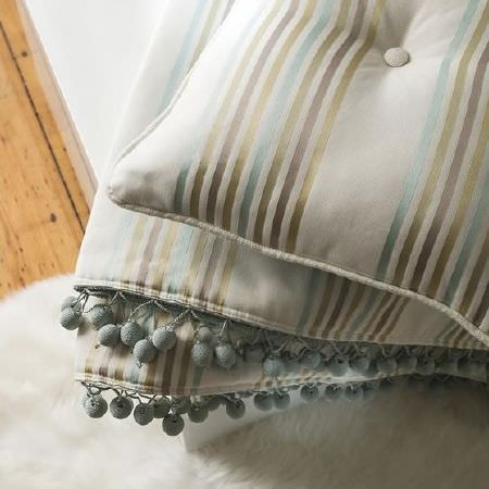 Prestigious Textiles -  Pemberley Fabric Collection - Cream fabric and cushion, both with thin bands of blue, green, grey and gold, with blue fringing on the fabric, on a fluffy white rug