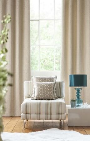 Prestigious Textiles -  Pemberley Fabric Collection - Long cream curtains, cream striped chair, cream and beige circle print cushions, white cube side table, turquoise glass-bottomed lamp
