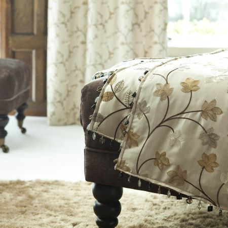 Prestigious Textiles -  Peony Gardens Fabric Collection - A white quilt with a classic flower stitching decoration on a brown upholstered footstoool