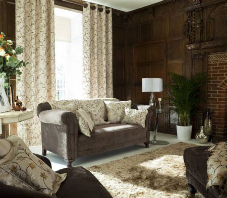 Prestigious Textiles -  Peony Gardens Fabric Collection - Beautiful white curtains with a vine pattern behind a grey upholstered classic couch with a white cover and pillows with floral designs