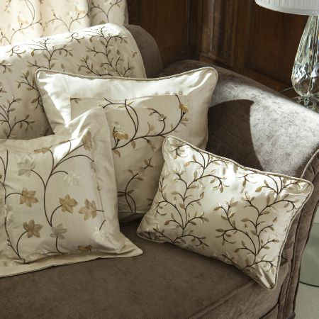 Prestigious Textiles -  Peony Gardens Fabric Collection - White cushions with a classic gold and silver vine and leaf pattern, on a brown upholstered couch with a white couch cover with vines