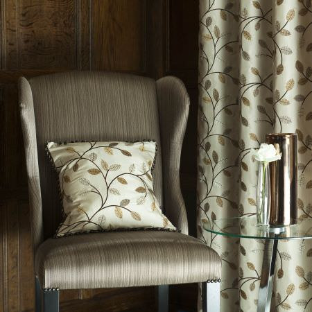 Prestigious Textiles -  Peony Gardens Fabric Collection - Classic white curtain and pillow with gold and silver leaf and vine pattern, and an easy chair with reflective grey upholstery