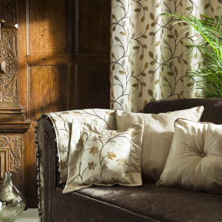 Prestigious Textiles -  Peony Gardens Fabric Collection - White curtain with a leaf and vine patttern in gold, white cushions with stripes and leaves on a brown upholstered couch for a classic house