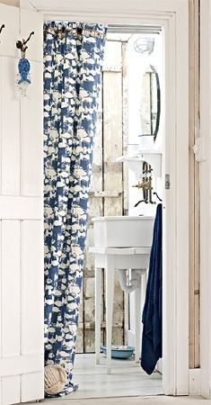 Prestigious Textiles -  Pickle Fabric Collection - A charcoal coloured cloth with a floor-length door curtain made with a small fish print in cream and dark shades of blue