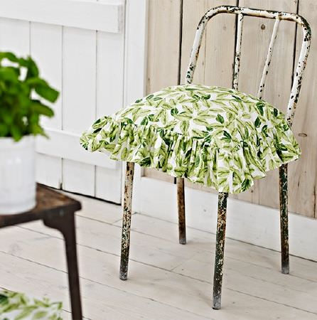 Prestigious Textiles -  Pickle Fabric Collection - A frilly leaf print square scatter cushion sitting on a rusty white metal chair, near a wooden table and white plant pot