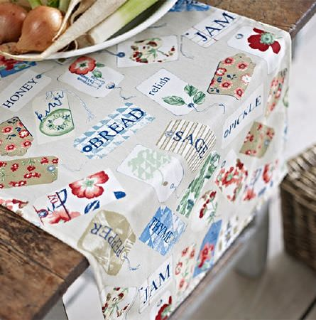 Prestigious Textiles -  Pickle Fabric Collection - A wooden table made with a fabric runner in grey, with a print of labels featuring storecupboard ingredients and florals