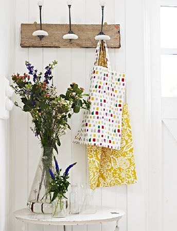 Prestigious Textiles -  Pickle Fabric Collection - A coat rack with two fabric bags featuring a dot print and a mustard yellow and white floral design, hanging above a table