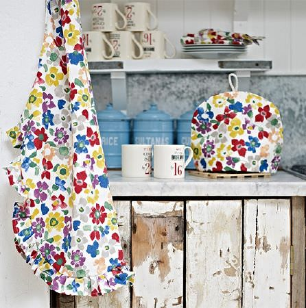 Prestigious Textiles -  Pickle Fabric Collection - Multicoloured stylised floral print fabric made into an apron and teacosy on a stone counter with mugs and distressed wood