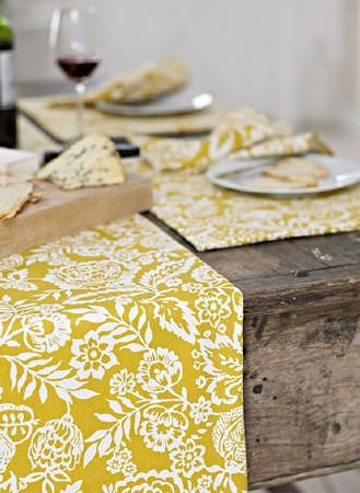 Prestigious Textiles -  Pickle Fabric Collection - A large, rustic, solid wood table with mustard yellow and white floral print table runners and placemats, with crockery