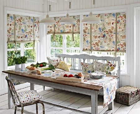 Prestigious Textiles -  Pickle Fabric Collection - A large wooden table with a bench seat and a wooden chair, with multicoloured patterned blinds, cushions and a table runner