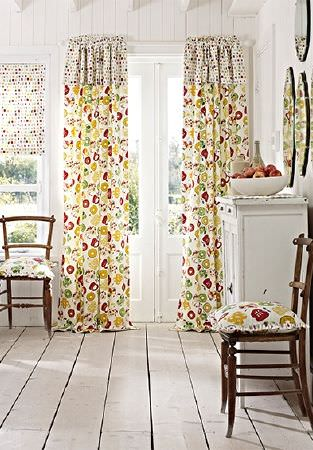 Prestigious Textiles -  Pickle Fabric Collection - Bright red, green and yellow coloured fruit print cushions and curtains with dotted trim and blinds, with simple wood chairs