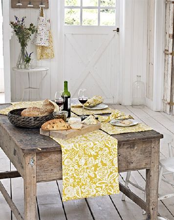 Prestigious Textiles -  Pickle Fabric Collection - Mustard yellow and white patterned table runner and placemats on a rustic wood table with a bowl, plates and glasses