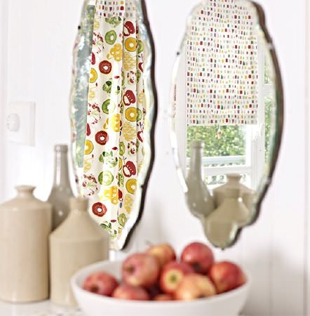 Prestigious Textiles -  Pickle Fabric Collection - Two mirrors with a dotted blind and a bright red, green and yellow fruit print curtain, with beige jars and a bowl of apples