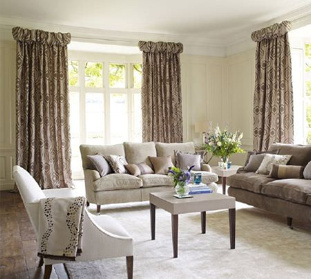 Prestigious Textiles -  Platinum Fabric Collection - Cream and light brown sofas with a white armchair, a cream table, light brown patterned curtains and cushions and vases