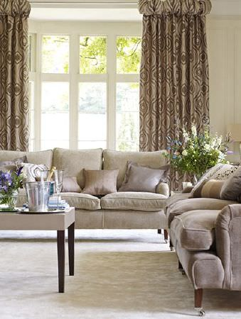 Prestigious Textiles -  Platinum Fabric Collection - Cream-brown sofas with wooden feet, a matching square coffee table, cream cushions and light brown patterned curtains