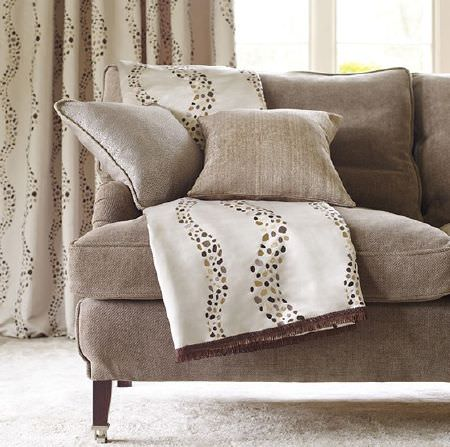 Prestigious Textiles -  Platinum Fabric Collection - A light brown sofa with two plain scatter cushions, a cream throw with dotted wavy lines and matching long curtains