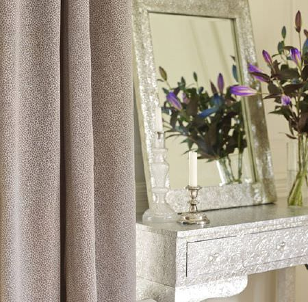 Prestigious Textiles -  Platinum Fabric Collection - Speckled brown and white curtains with a grey-white side table with a silver framed mirror and two candlestick holders