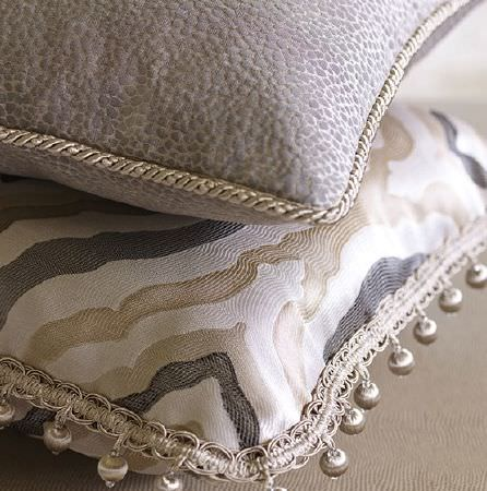 Prestigious Textiles -  Platinum Fabric Collection - Silver balls fringing a grey, white and beige patterned cushion, beneath a speckled grey-white cushion with cream cord