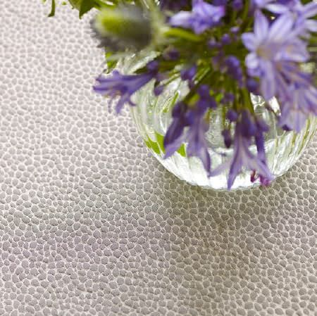 Prestigious Textiles -  Platinum Fabric Collection - A round glass vase holding purple flowers on a light grey and white coloured slightly speckled surface