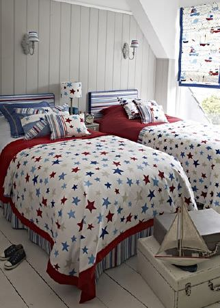 Prestigious Textiles -  Playtime Fabric Collection - Dark red, navy, beige and white star and stripe print fabrics making up blinds, throws, cushions and bedding on two beds