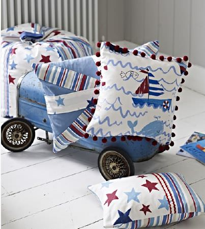Prestigious Textiles -  Playtime Fabric Collection - Cushions and a beanbag covered with white, blue and red fabrics with sea themes, stripes and stars, with a vintage toy car