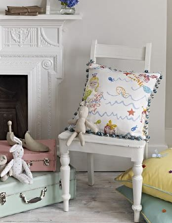 Prestigious Textiles -  Playtime Fabric Collection - A white chair with a mermaid and fish print scatter cushion, two pastel coloured suitcases, and two plain cushions