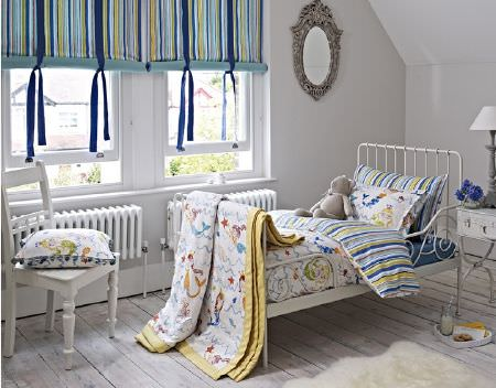 Prestigious Textiles -  Playtime Fabric Collection - Striped and patterned fabrics in white, green and shades of blue on a throw, blind and bedding on a white metal framed bed