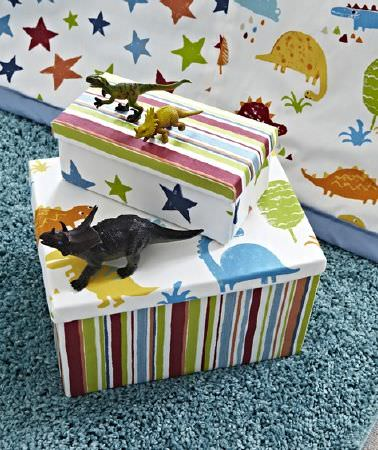 Prestigious Textiles -  Playtime Fabric Collection - A dinosaur print throw with a fluffy dusky blue rug and two boxes covered with dinosaur patterns and multicoloured stripes