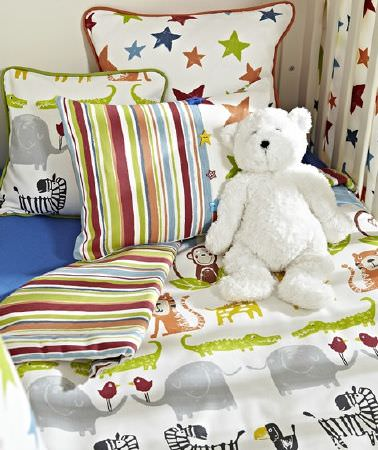 Prestigious Textiles -  Playtime Fabric Collection - A bed with blue sheets, a double sided duvet and scatter cushions with stripes, stars and multicoloured wild animal prints