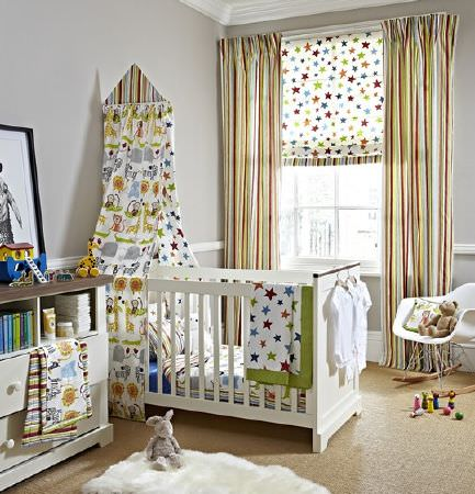 Prestigious Textiles -  Playtime Fabric Collection - A white cot with a wild animal print canopy, multicoloured striped curtains, a star print blind and throw, and a rug