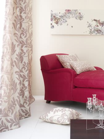 Prestigious Textiles -  Portland Fabric Collection - Light silvery curtain with a classic foliage pattern, and silvery cushions on a red upholstered easy chair