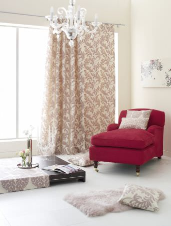 Prestigious Textiles -  Portland Fabric Collection - Champagne coloured curtain with a classic foliage design, a tablecloth and cushions with a classic pattern, and a red upholstered easy chair