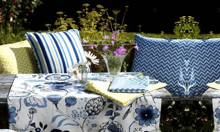Prestigious Textiles -  Potting Shed Fabric Collection - Outdoor eating - blue and white large print tablecloth, striped and zigzag cushions in shades of blue, green and blue table linen