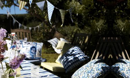 Prestigious Textiles -  Potting Shed Fabric Collection - Picnic table, striped blue, green and white tabelcloth with floral cushions in shades of blue