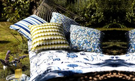 Prestigious Textiles -  Potting Shed Fabric Collection - Relax in the hammock - selection of comfy cushions, striped, floral and spotted designs in greens/blues, with white and blue patterned throw