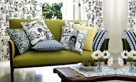 Prestigious Textiles -  Potting Shed Fabric Collection - Potting Shed Collection indoors! Green sofa with range of cushion designs in blue and green - zigzag, spotted, floral, tree motif