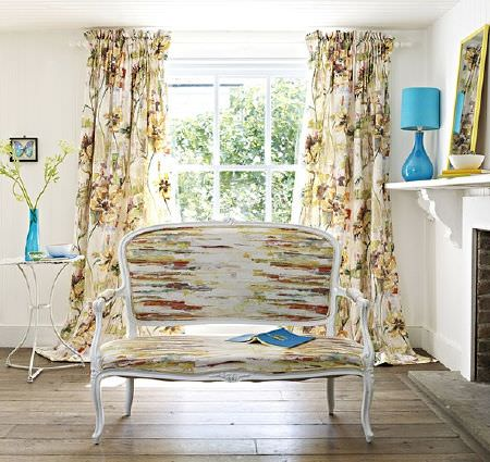 Prestigious Textiles -  Printworks Fabric Collection - Red, gold and green streaks and florals on white curtains anda sofa with a white wood frame, with an aqua blue lamp