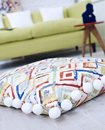 Prestigious Textiles -  Printworks Fabric Collection - White pompoms edging a blue, orange and white patterned cushion in front of a small round table and a light green sofa