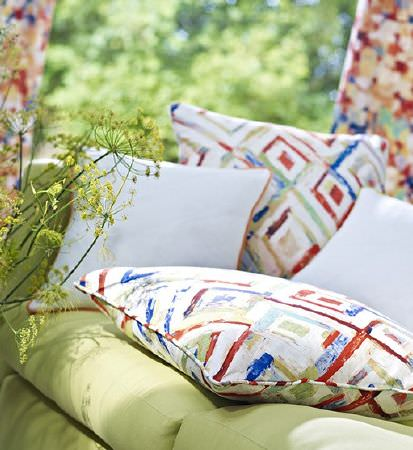 Prestigious Textiles -  Printworks Fabric Collection - Plain white and orange, blue and white scatter cushions on a light green sofa in front of bright multicoloured curtains